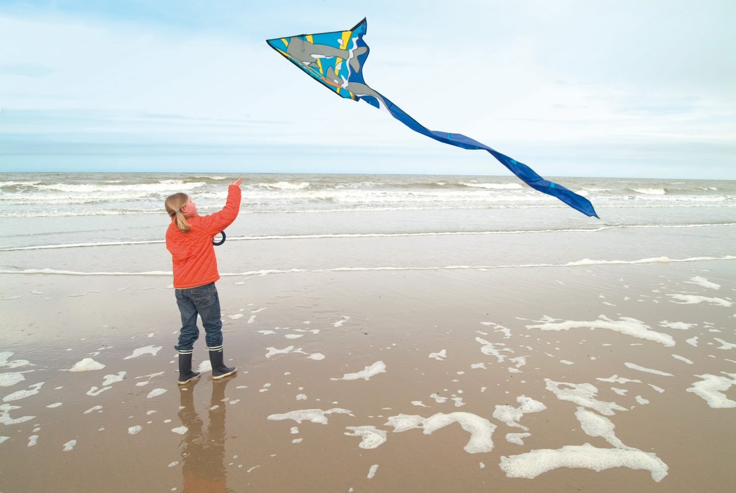 young girl flying a kite on the beach